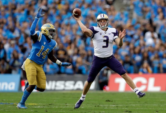 Washington quarterback Jake Browning (3) throws as UCLA linebacker Krys Barnes (14) chases.