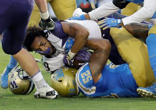 Washington running back Myles Gaskin (top) loses his helmet as he is tackled by UCLA linebacker Lokeni Toailoa (52).