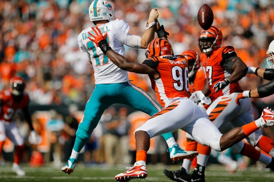 Cincinnati Bengals defensive end Carlos Dunlap (96) strips the ball from Miami Dolphins quarterback Ryan Tannehill (17) on the run in the fourth quarter of the NFL Week 5 game between the Cincinnati Bengals and the Miami Dolphins at Paul Brown Stadium in downtown Cincinnati on Sunday, Oct. 7, 2018. The Bengals overcame a 14-0 deficit to win 27-17.