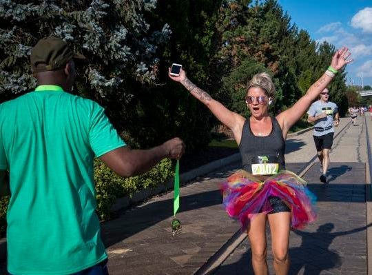 A Margarita Madness 5K finisher gets her medal at the end of the race through Sawyer Point Saturday in Cincinnati.