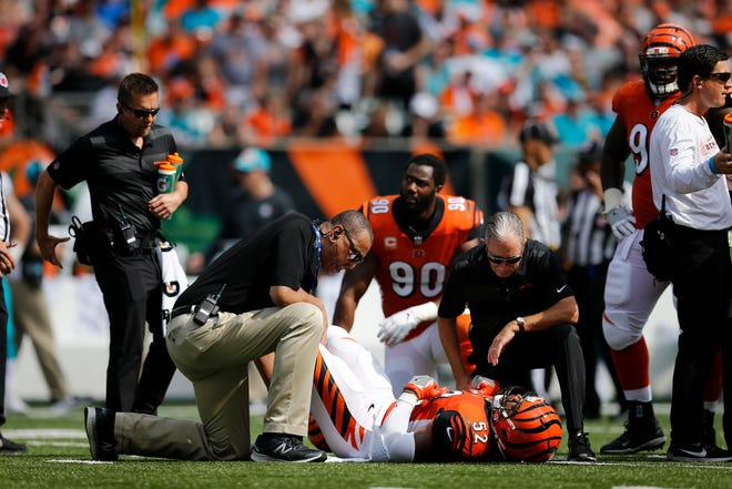 Cincinnati Bengals linebacker Preston Brown (52) is examined on the field for an injury in the second quarter of the NFL Week 5 game between the Cincinnati Bengals and the Miami Dolphins at Paul Brown Stadium in downtown Cincinnati on Sunday, Oct. 7, 2018. The Dolphins led 14-0 at halftime.