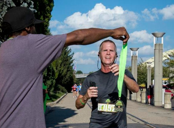 A Margarita Madness 5K finisher gets his medal at the end of the race through Sawyer Point Saturday in Cincinnati.