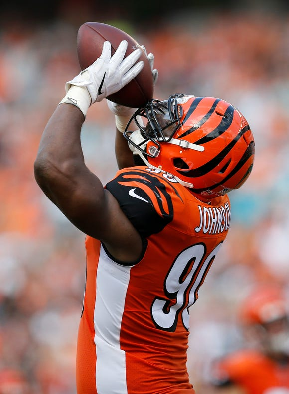 Cincinnati Bengals defensive end Michael Johnson (90) celebrates in the style of injured tight end Tyler Eifert (85) after returning an interception for a touchdown in the fourth quarter of the NFL Week 5 game between the Cincinnati Bengals and the Miami Dolphins at Paul Brown Stadium in downtown Cincinnati on Sunday, Oct. 7, 2018. The Bengals overcame a 14-0 deficit to win 27-17.