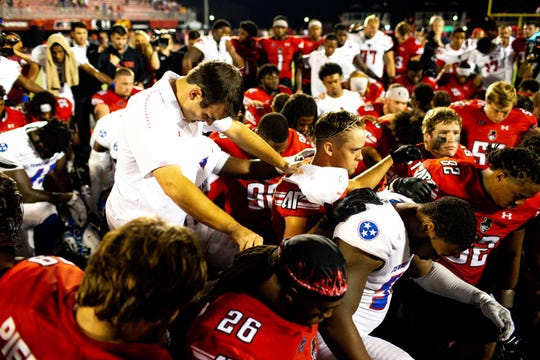 Austin Peay Governors head coach Will Healy prays with players from Austin Peay Governors and Tennessee State Tigers for Tennessee State Tigers linebacker Christion Abercrombie (6) after the game at Fortera Stadium Saturday, Oct. 6, 2018, in Clarksville, Tenn.