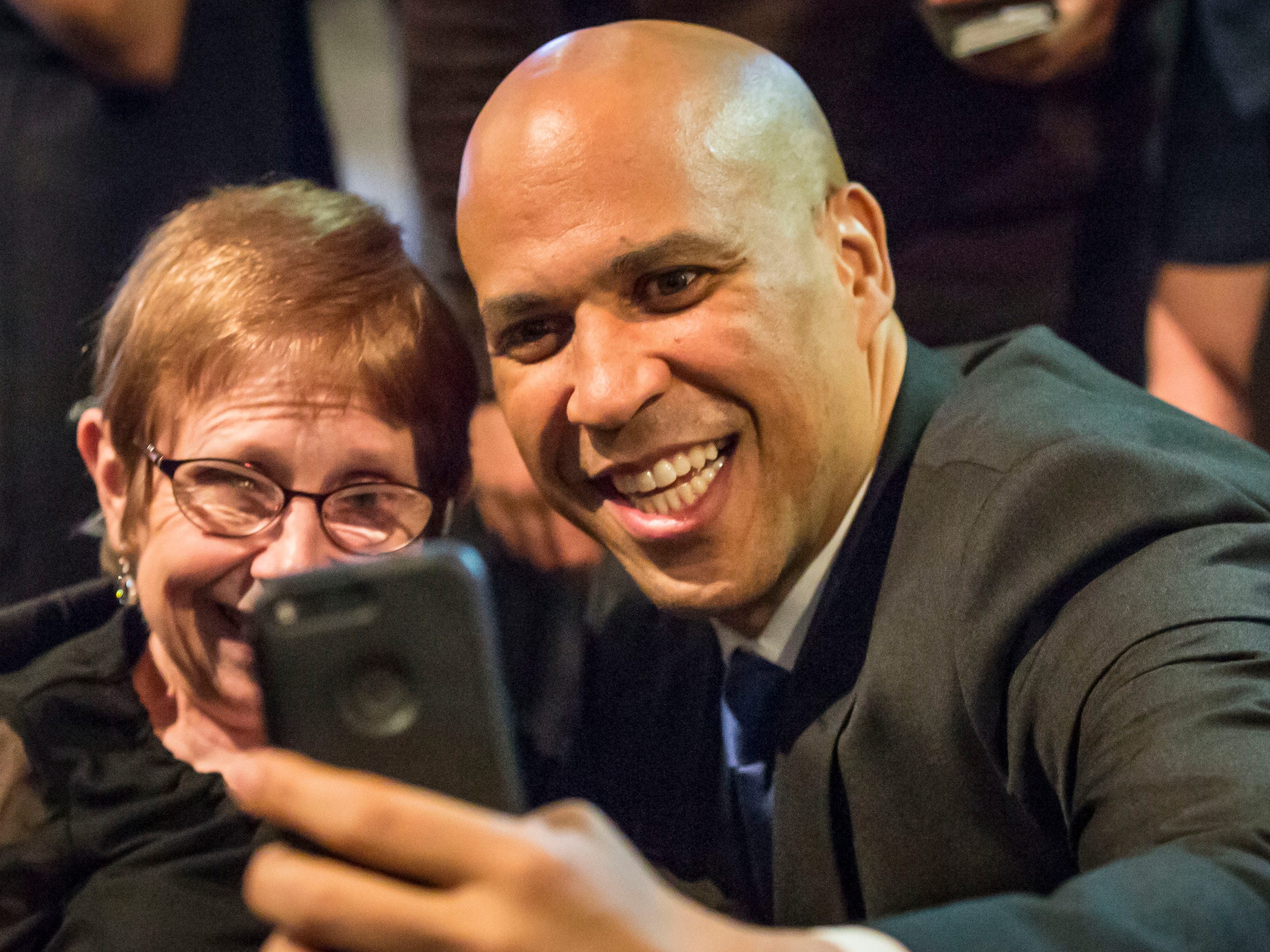 New Jersey Sen. Cory Booker takes selfies with audience members at the Iowa Democratic Party's fall gala Saturday, Oct. 6, 2018, at the Iowa Events Center in Des Moines.