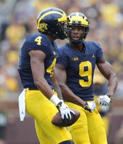 Michigan's Nico Collins (4) celebrates with Donovan Peoples-Jones after his first-down catch against Maryland, Saturday, Oct. 6, 2018 at Michigan Stadium.
