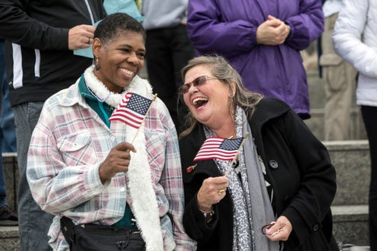 Teresa Goin, 49, left, and Laurel Brandon, 63, both of Waterford, sing God Bless America after praying the Rosary on the Detroit Riverwalk, during Rosary Coast to Coast in Detroit, Mich., Sunday, Oct 7, 2018.