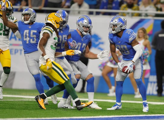 Detroit Lions' Jamal Agnew, right, downs a punt after it hit a Packer in the first quarter Sunday, Oct. 7, 2018 at Ford Field. The play was ruled a fumble and the Lions got the ball at the 1-yard line.