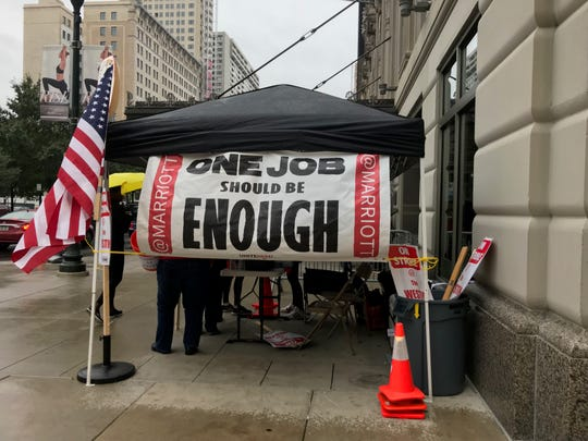 A sign that reads, 'One Job Should Be Enough,' hung from a tent outside the Westin Book Cadillac as hotel workers represented by UNITE HERE Local 24 begin their strike on Sunday, Oct. 7 for fair wages, better insurance plans and more.