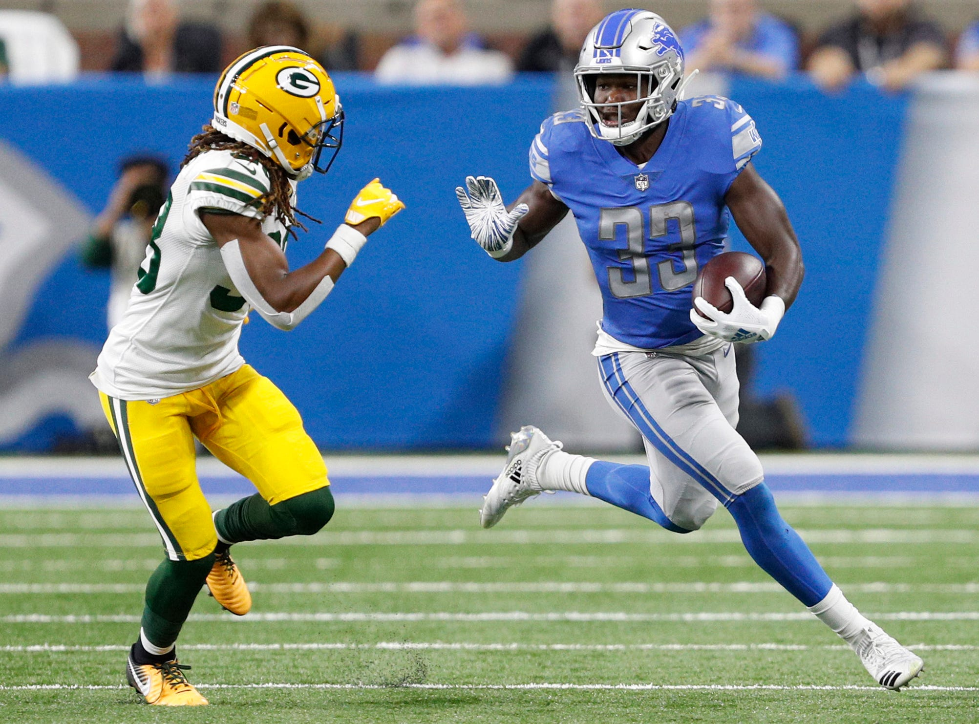 Lions running back Kerryon Johnson runs the ball against Packers cornerback Tramon Williams during the first half on Sunday, Oct. 7, 2018, at Ford Field.