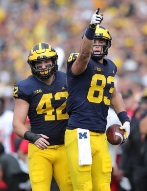 Michigan's Zach Gentry (83) celebrates his first-down catch against Maryland during the first half Saturday, Oct. 6, 2018 at Michigan Stadium. Fullback Ben Mason is in the background.