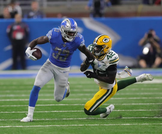 Detroit Lions' Kerryon Johnson runs by the Green Bay Packers' Oren Burks during the second half Sunday, Oct. 7, 2018 at Ford Field.