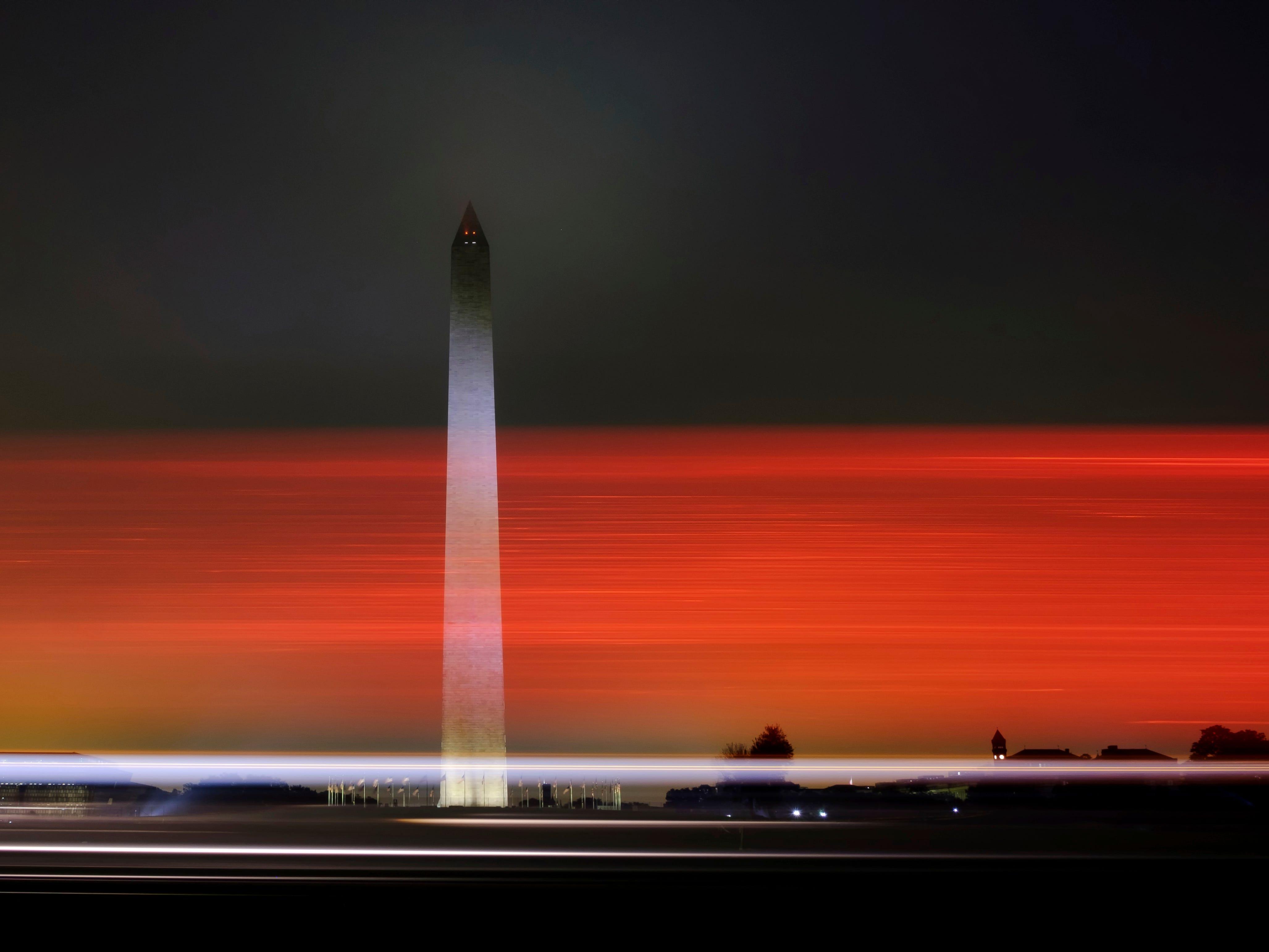 Early morning traffic streaks past the Washington Monument before daybreak Sunday, Oct. 7, 2018, in Washington.