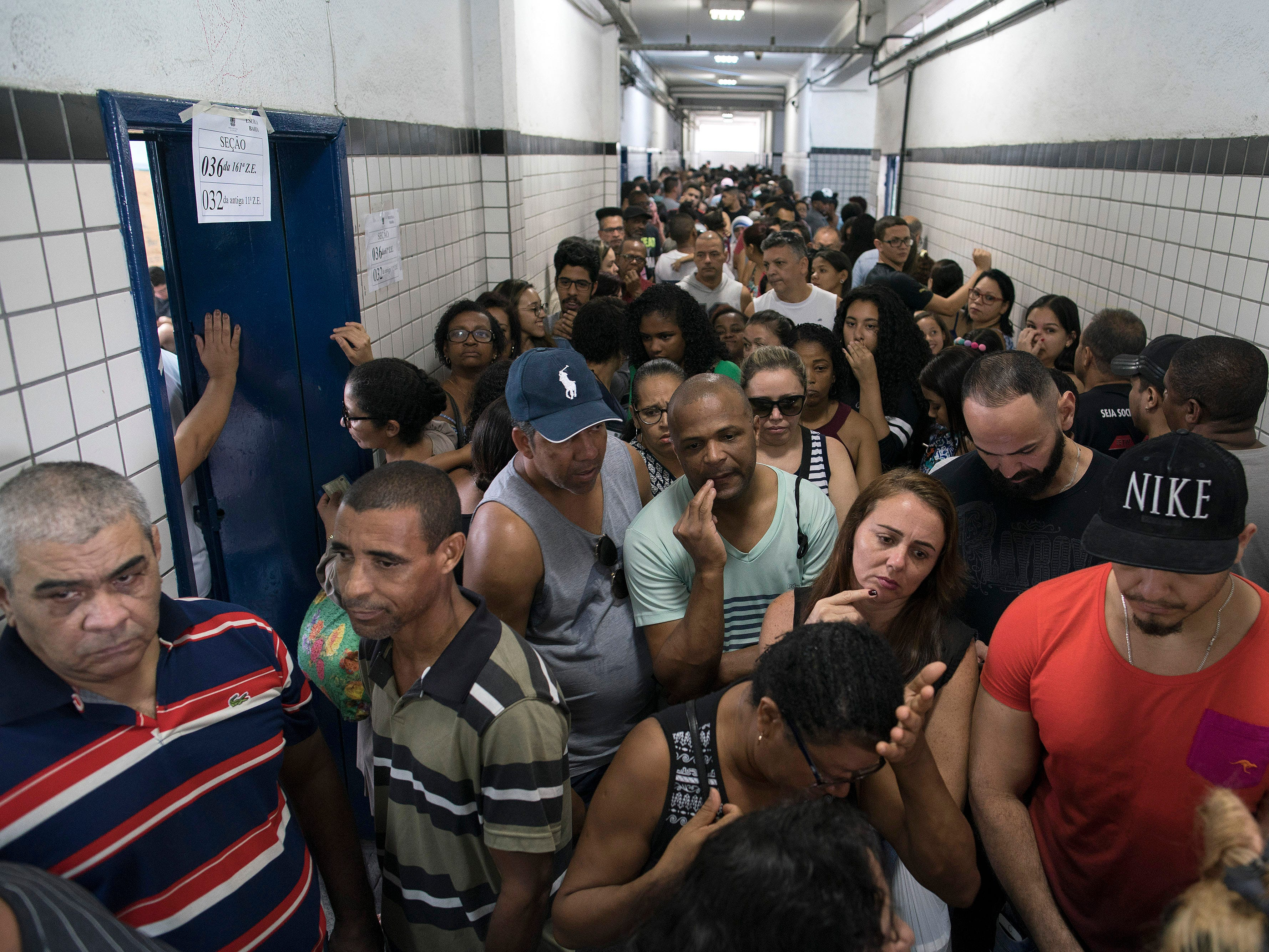 People wait in line to vote in the general election at a polling station in the Mare Complex slum in Rio de Janeiro, Brazil, Sunday, Oct. 7, 2018.  Brazilians choose among 13 candidates for president Sunday in one of the most unpredictable and divisive elections in decades. If no one gets a majority in the first round, the top two candidates will compete in a runoff.