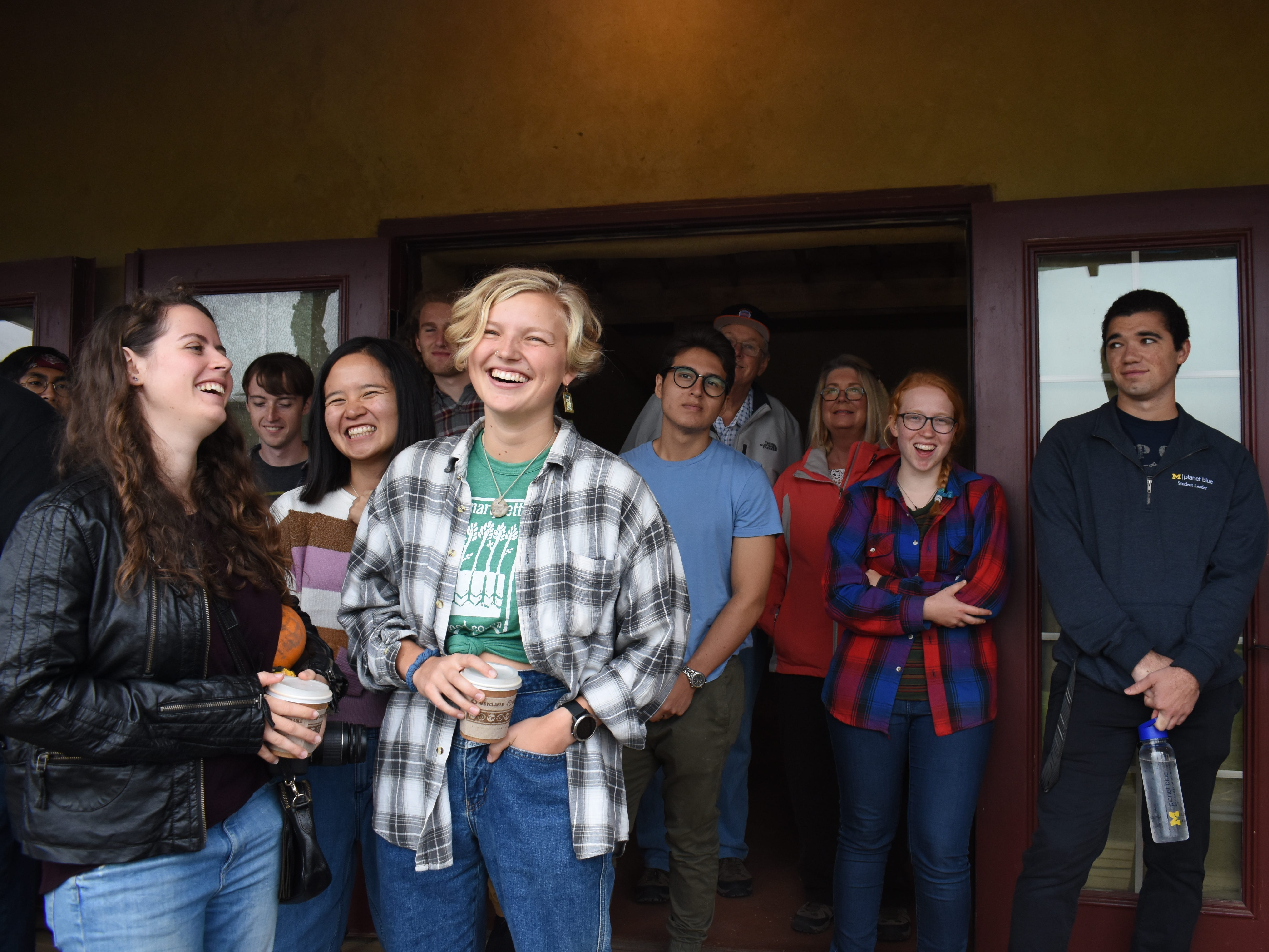 Students, many of whom built the Straw Bale House themselves, line the porch with other visitors to listen to a brief ceremony celebrating the building's  public unveiling.