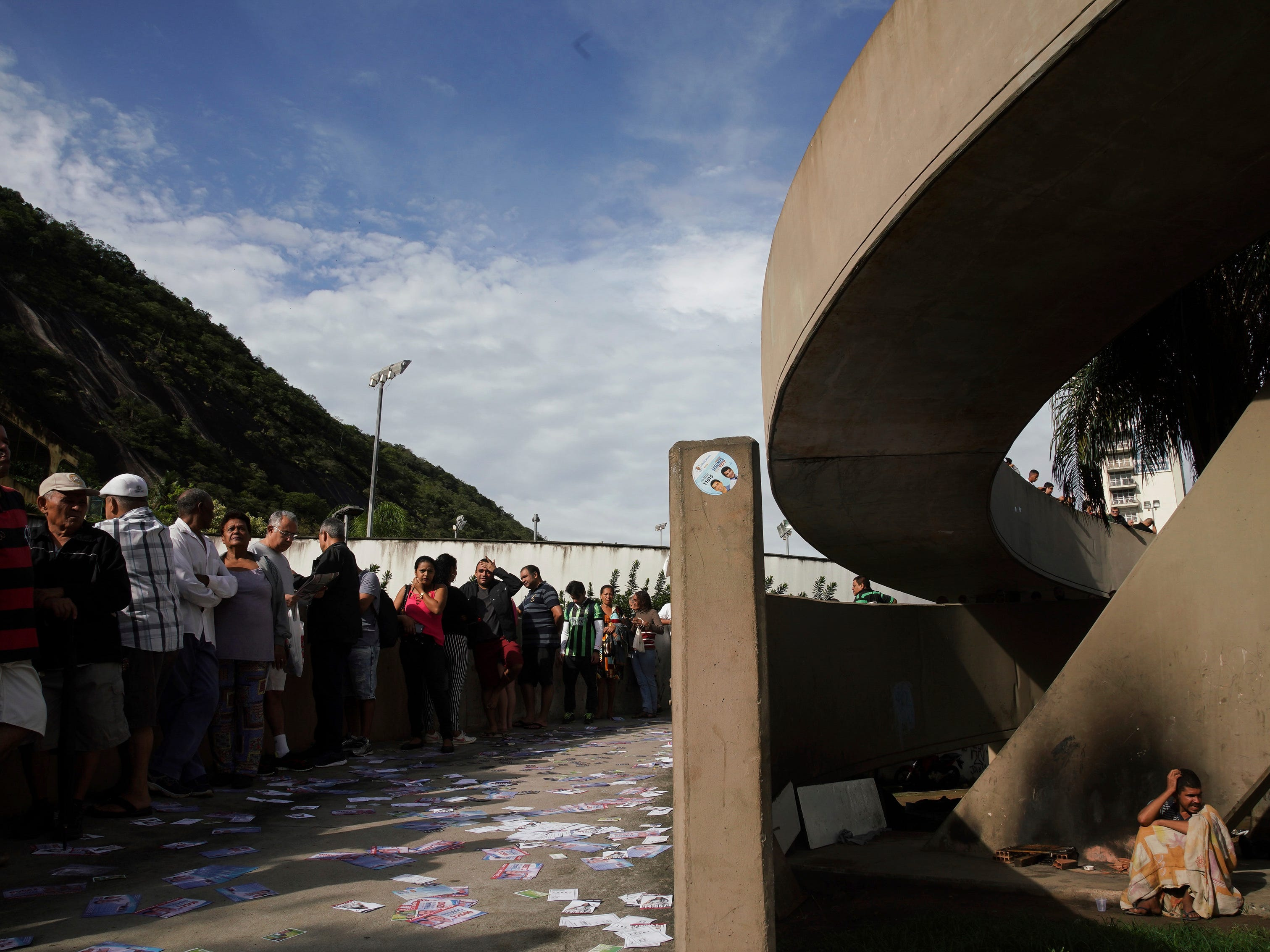 A homeless person sits underneath a bridge where he spent the night as voters wait in line at a polling station in the Rocinha favela in Rio de Janeiro, Brazil, Sunday, Oct. 7, 2018. Brazilians choose among 13 candidates for president Sunday in one of the most unpredictable and divisive elections in decades. If no one gets a majority in the first round, the top two candidates will compete in a runoff.