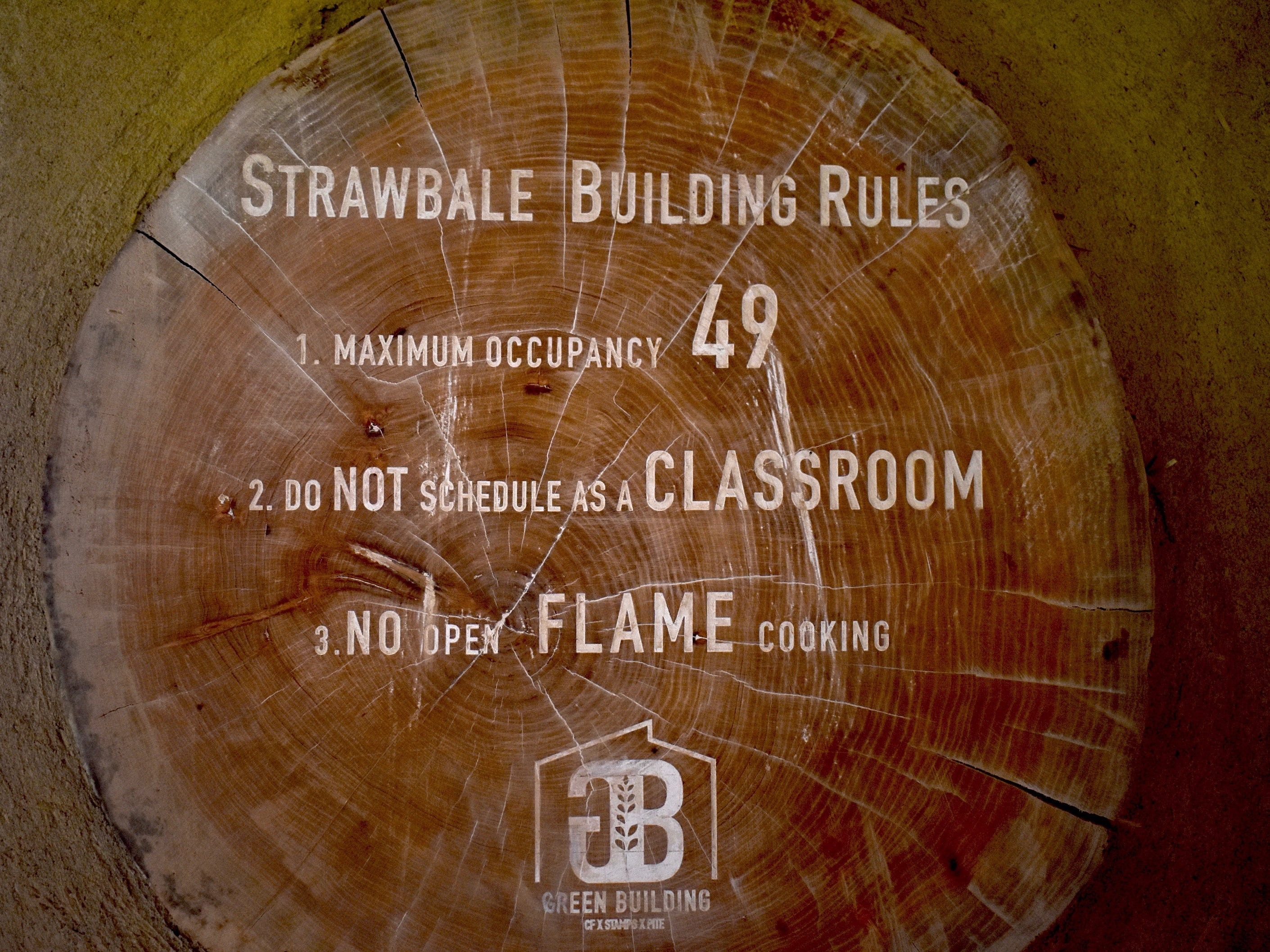 Crafted of natural materials like straw, wood, sand, and clay, the Straw Bale Building boasts informational plaques that are carved into tree slices.