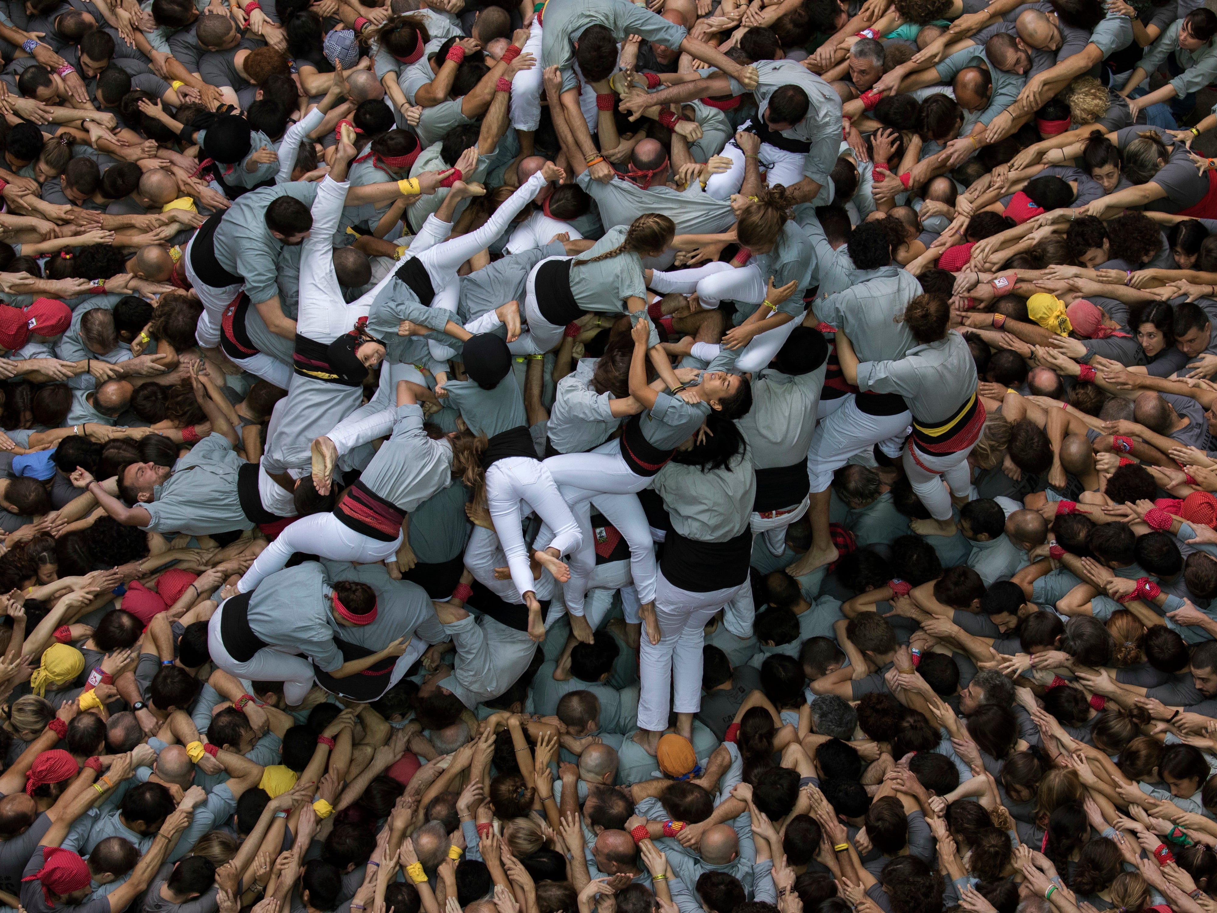 """Members of """"Castellers de Sants"""" fall as they try to complete their human tower during the 27th Human Tower Competition in Tarragona, Spain, on Sunday, Oct. 7, 2018. The tradition of building human towers or """"castells"""" dates back to the 18th century and takes place during festivals in Catalonia, where """"colles"""" or teams compete to build the tallest and most complicated towers. """"Castells"""" were declared by UNESCO one of the Masterpieces of the Oral and Intangible Heritage of Humanity."""