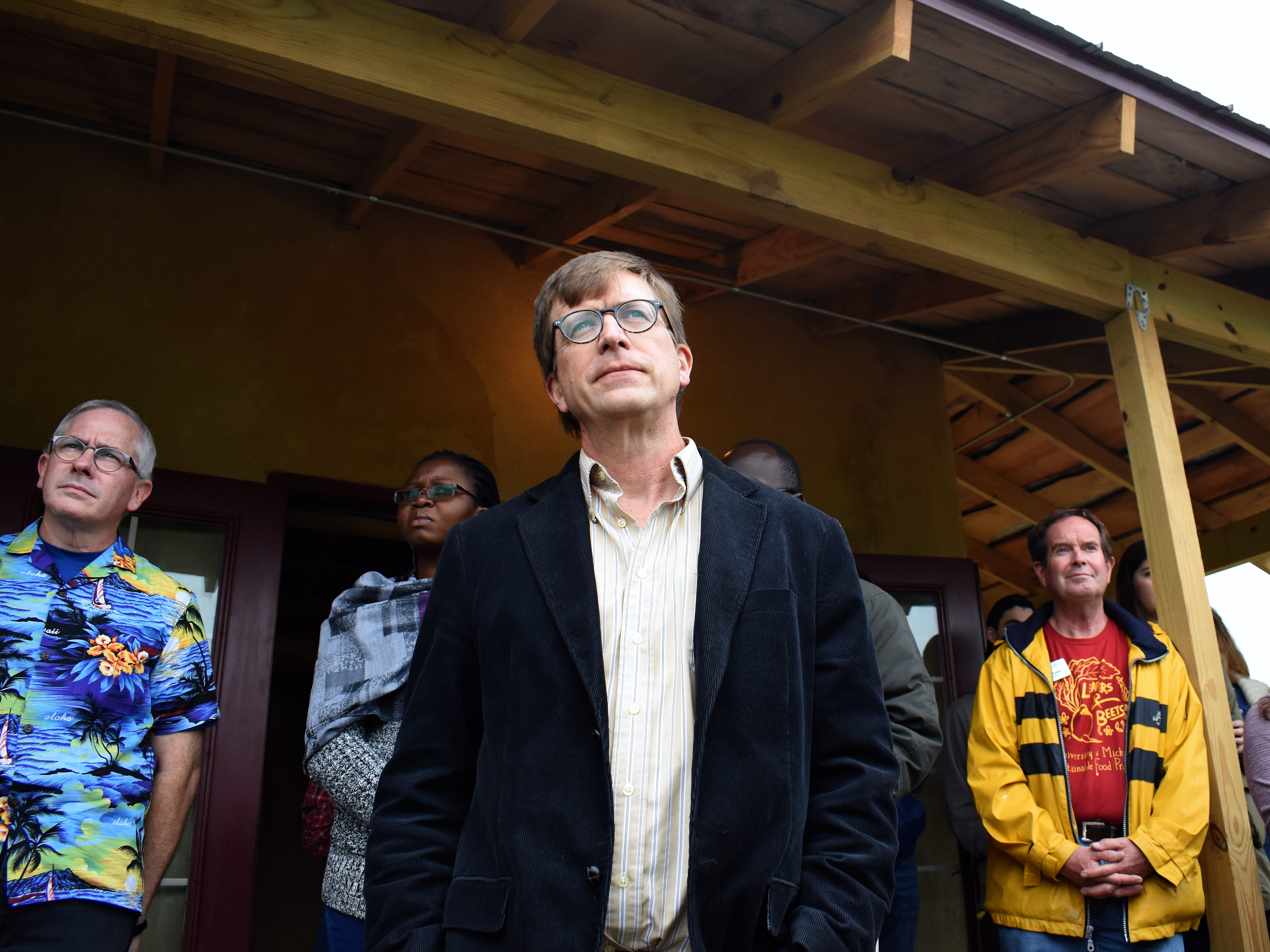 With visitors lining the porch, Art & Design Associate Professor Joe Trumpey, center, who led UM students in the creation of the Straw Bale Building, listens to speakers during a brief ceremony celebrating the natural building's public unveiling.