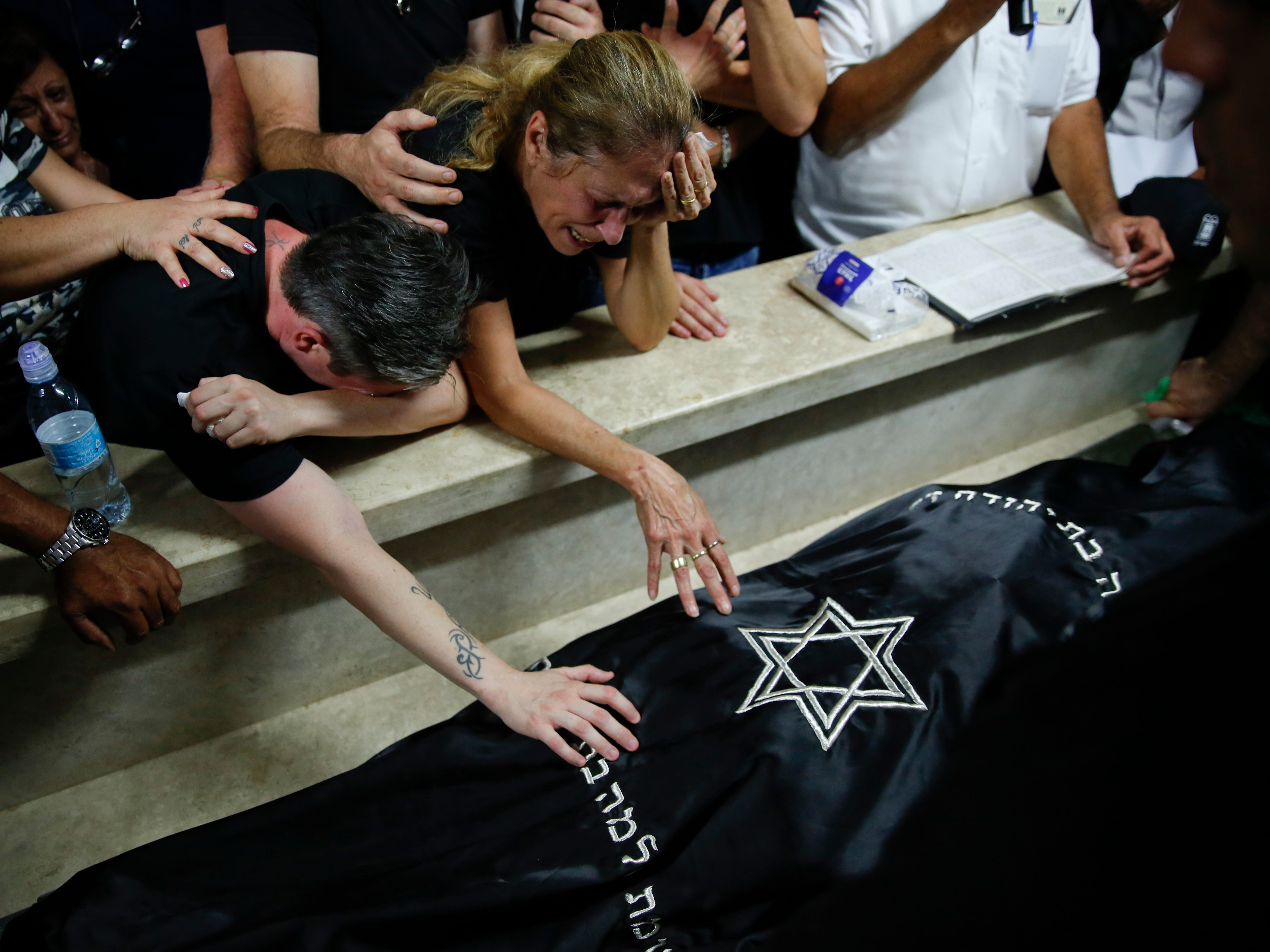 Hava Yehezkel, center, mourns next to the body of he daughter Kim during her funeral in in Rosh HaAyin, Israel, Monday, Oct. 8, 2018. Kim, 28, was killed after a Palestinian attacker opened fire at an  Israeli-Palestinian industrial zone in the West Bank Sunday, killing two Israelis and seriously wounding a third, the military said.