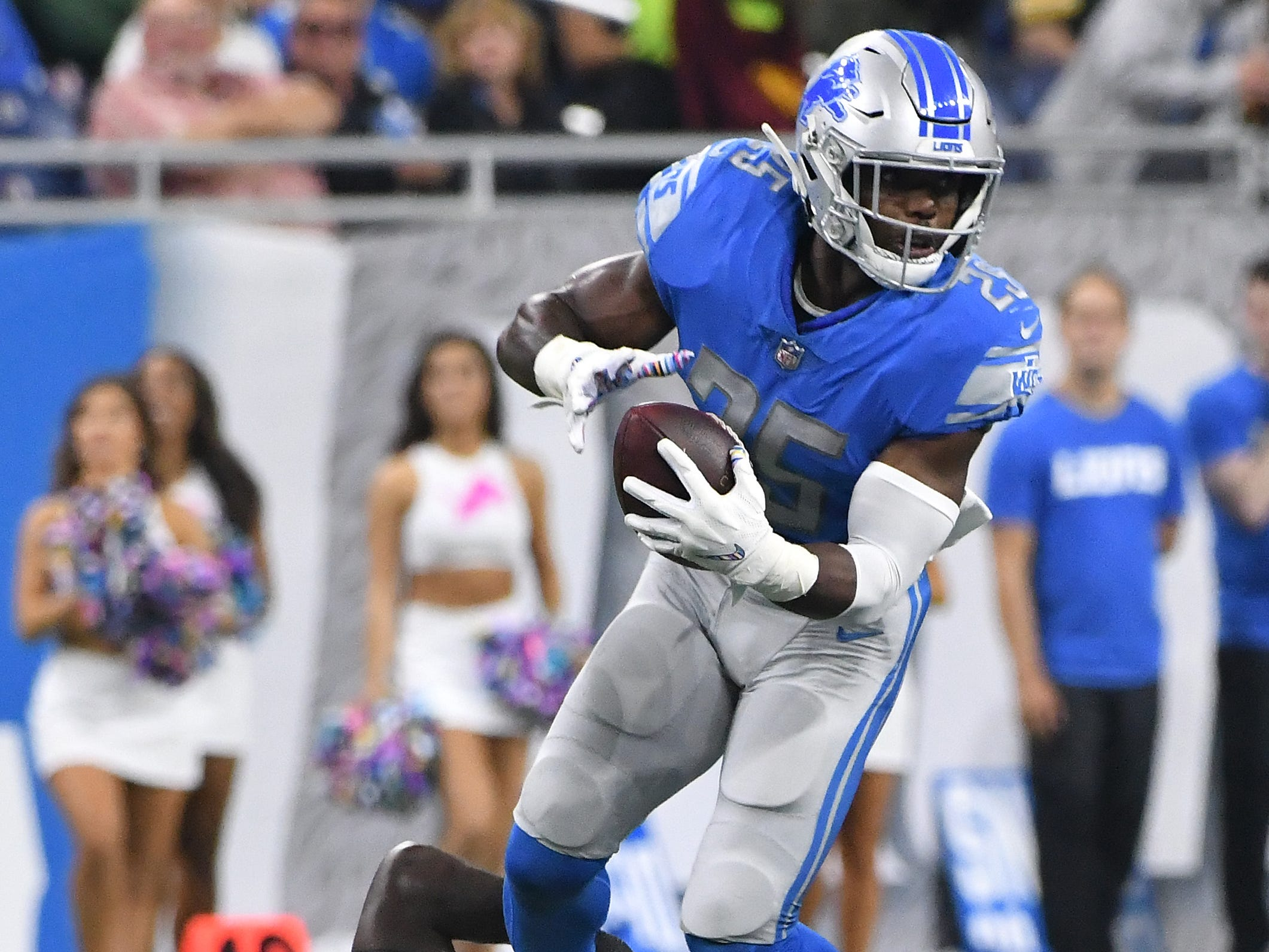 Lions running back Theo Riddick tries to break the grasp of Packers' Oren Burks in the second quarter.