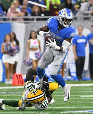 Lions running back Theo Riddick tries to break the grasp of Packers' Oren Burks in the second quarter of the game this month.