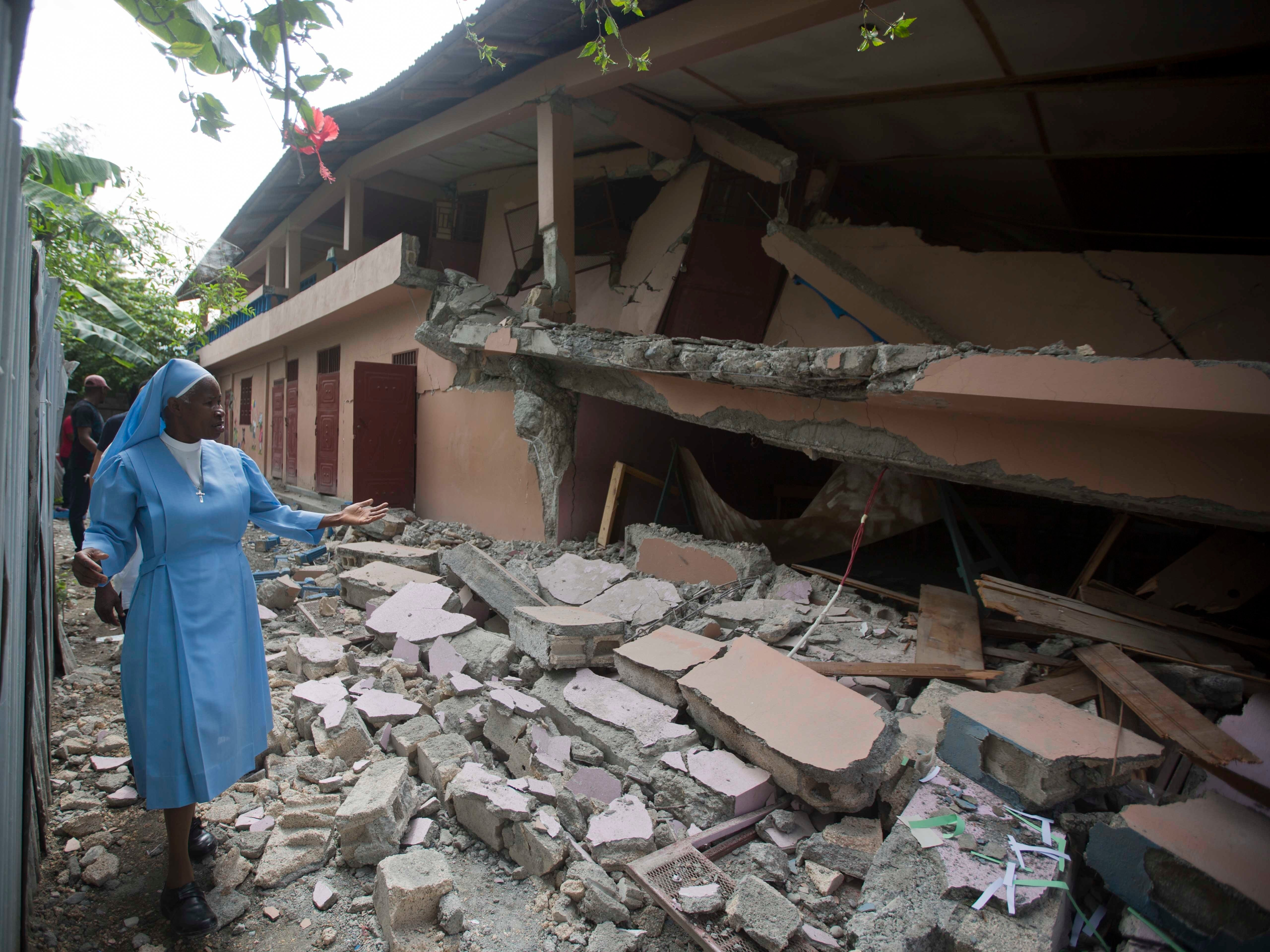 Sr Maryse Alsaint walks alongside a school damaged by a magnitude 5.9 earthquake the night before, in Gros Morne, Haiti, Sunday, Oct. 7, 2018. Emergency teams worked to provide relief in Haiti on Sunday after the quake killed at least 12 people and left dozens injured.