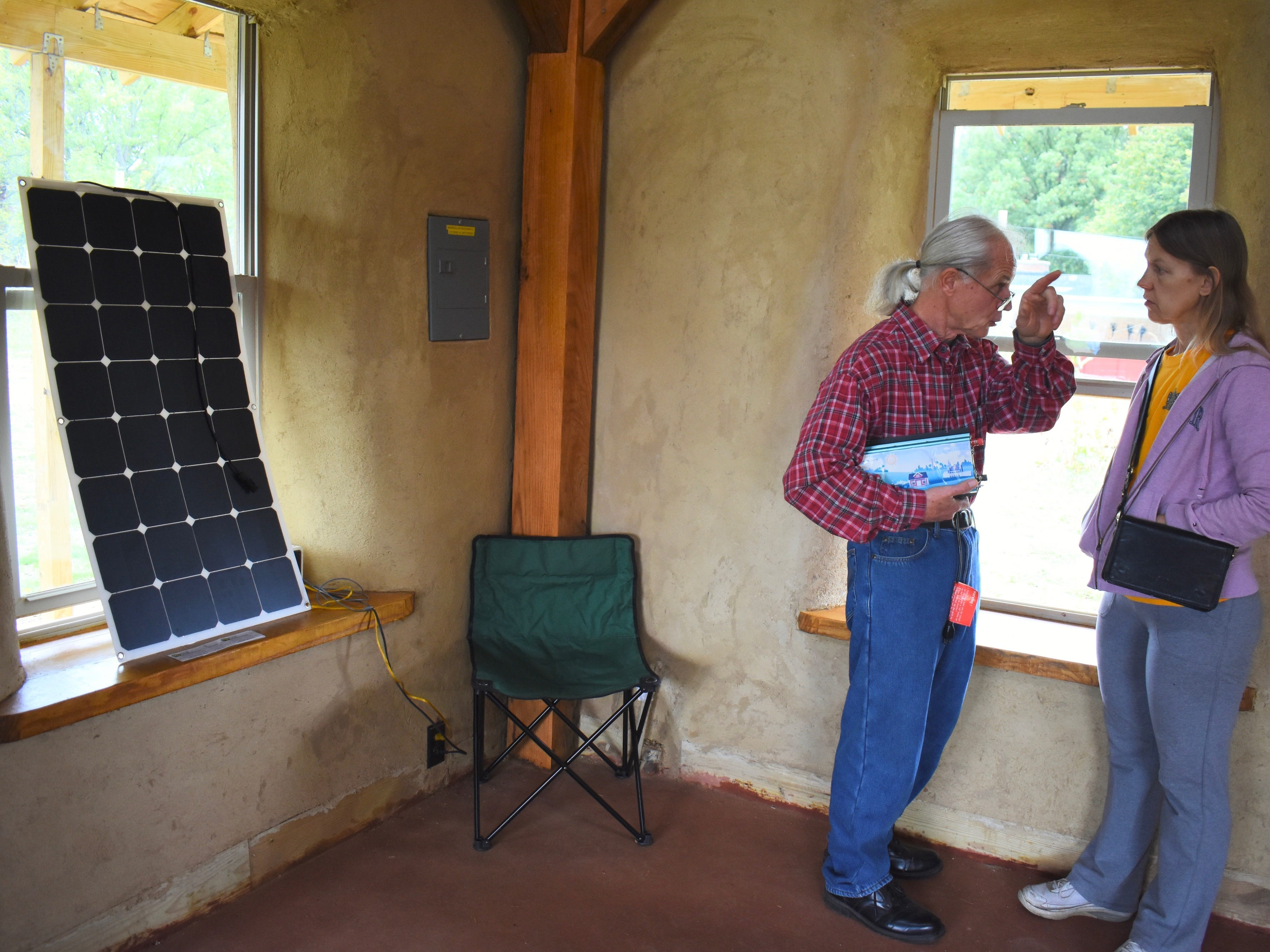 Standing next to a solar powered system that provides electricity to the Straw Bale Building, Michigan Energy Works Owner Chad Lampkin, left, talks about the set-up with Selena Lucas, who is planning on building an off-the-grid straw house of her own.