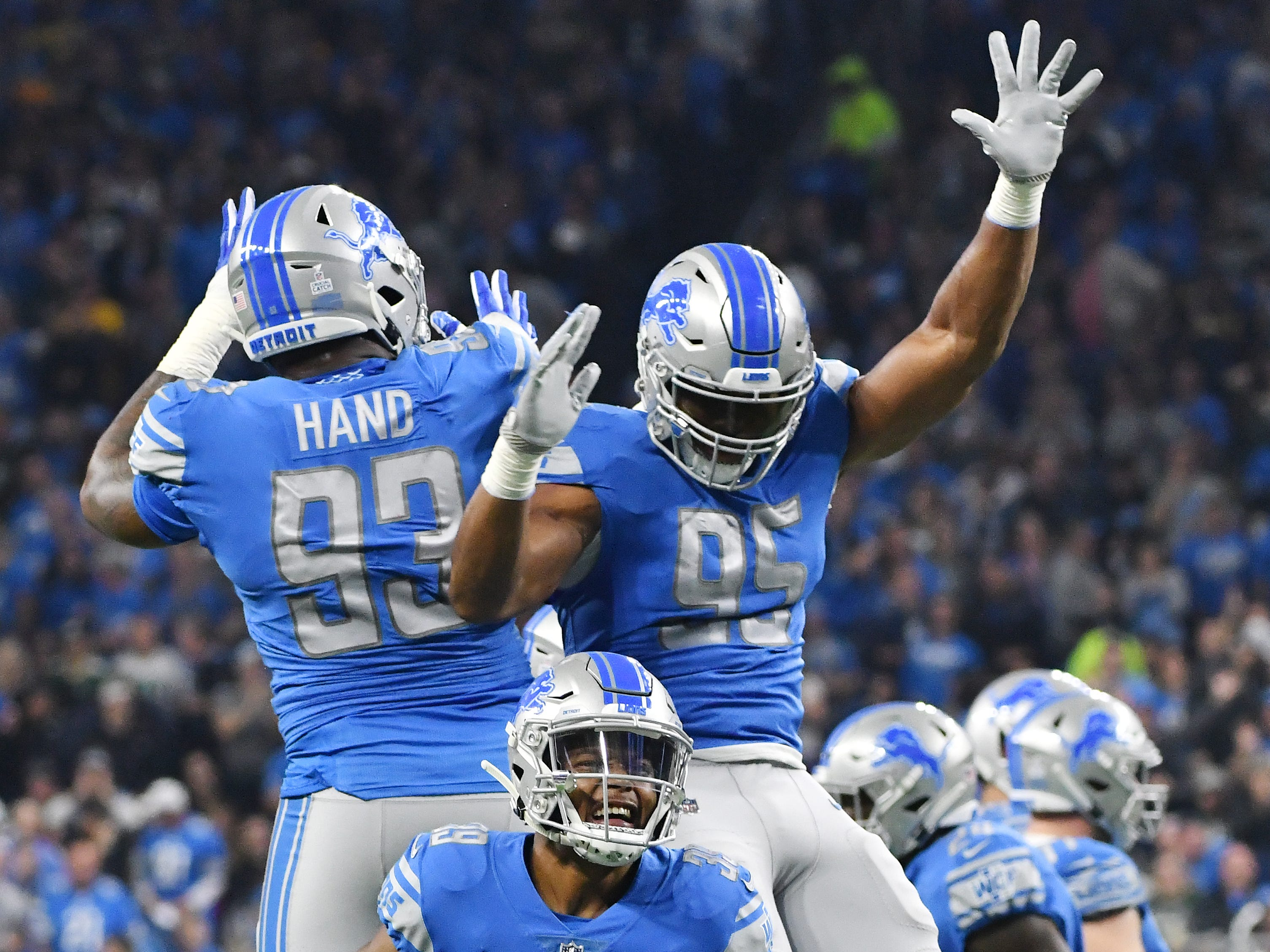 Lions' Da'Shawn Hand, Romeo Okwara and Jamal Agnew celebrate after Hand forced a fumble by Packers quarterback Aaron Rodgers which Detroit recovers in the first quarter.