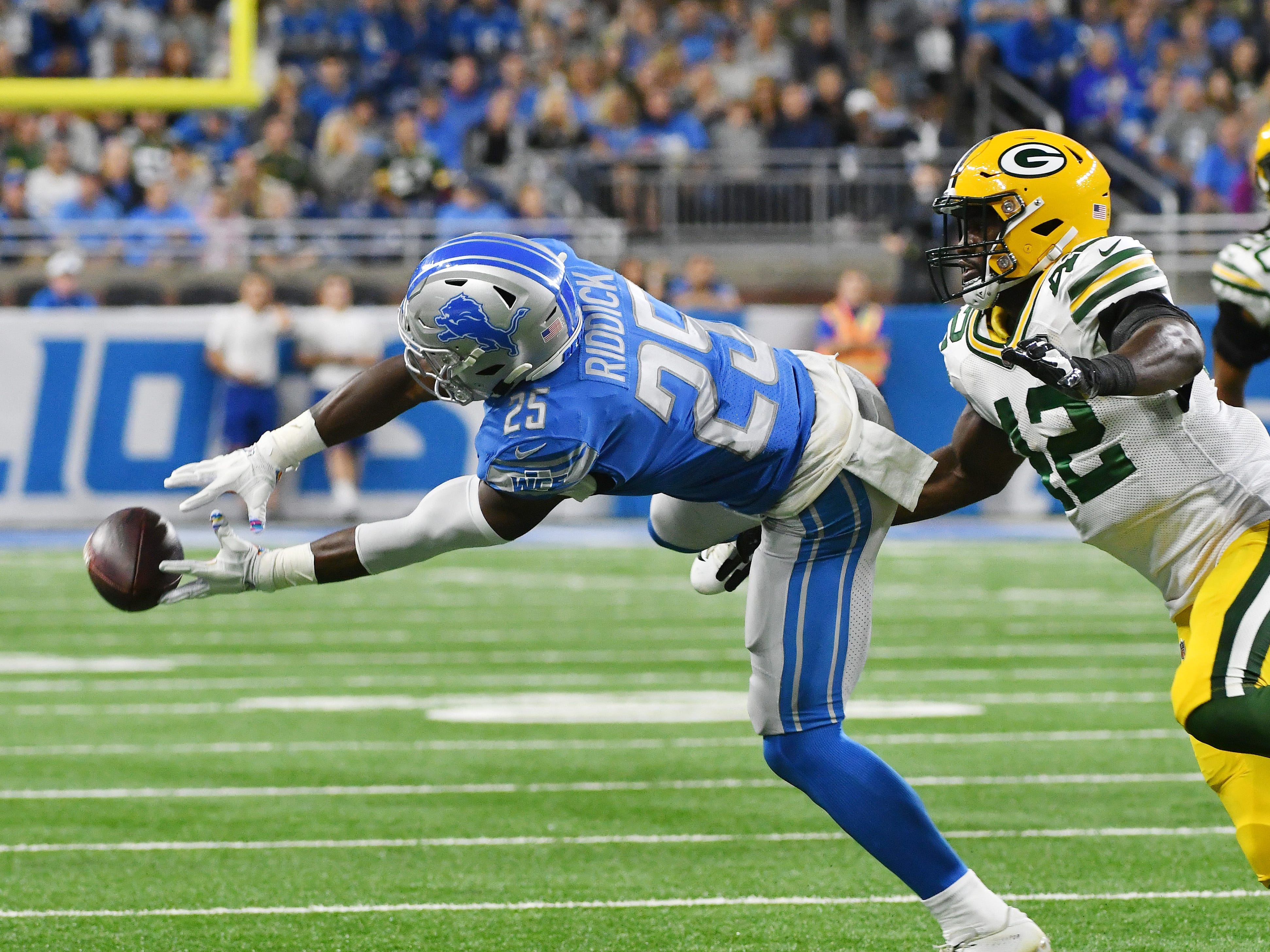 Lions running back Theo Ridick can't pull in a reception with Packers' Oren Burks defending in the first quarter.