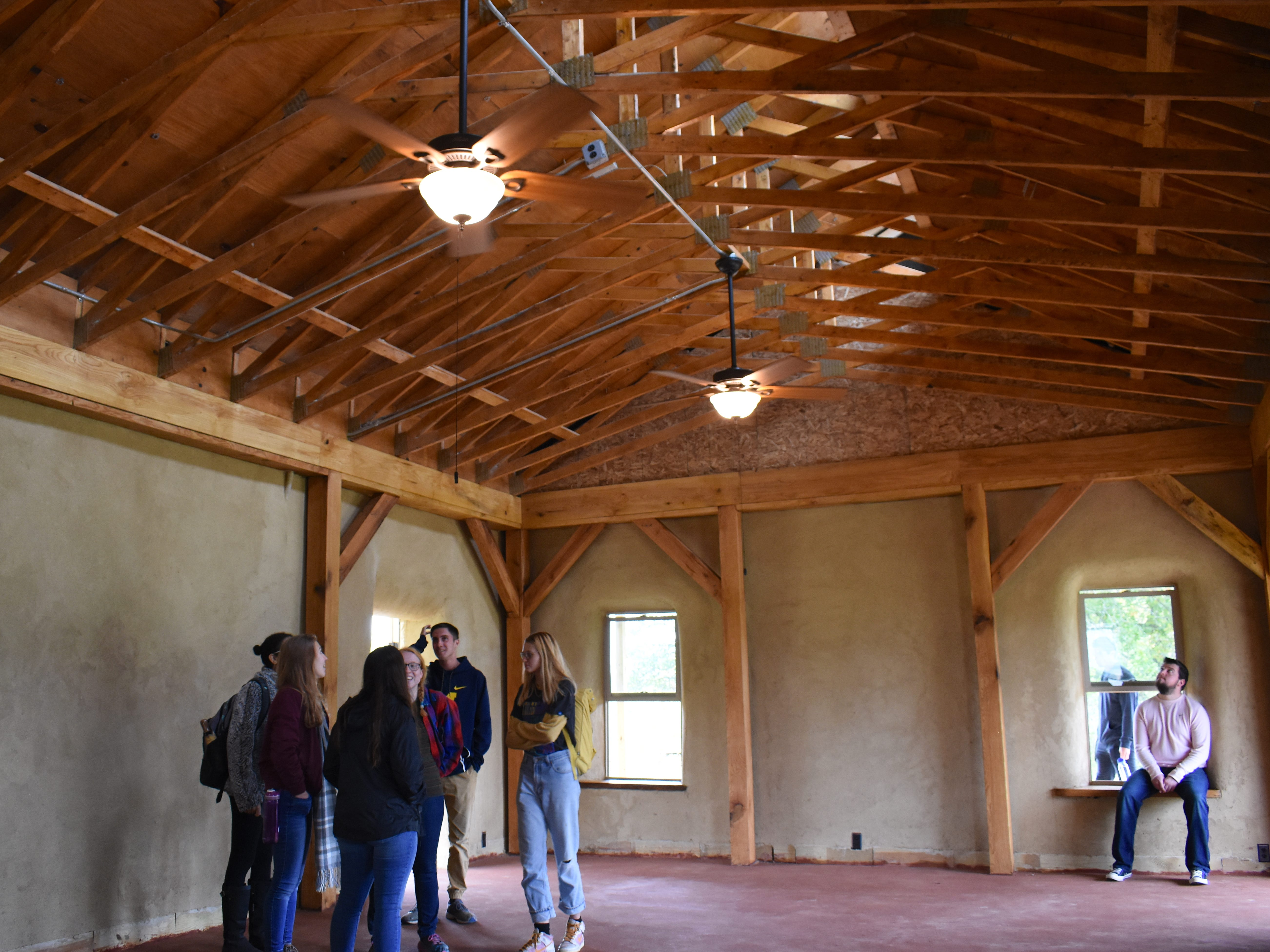 Visitors take a look at the interior of the off-the-grid Straw Bale Building at the Campus Farm in Ann Arbor Sunday.
