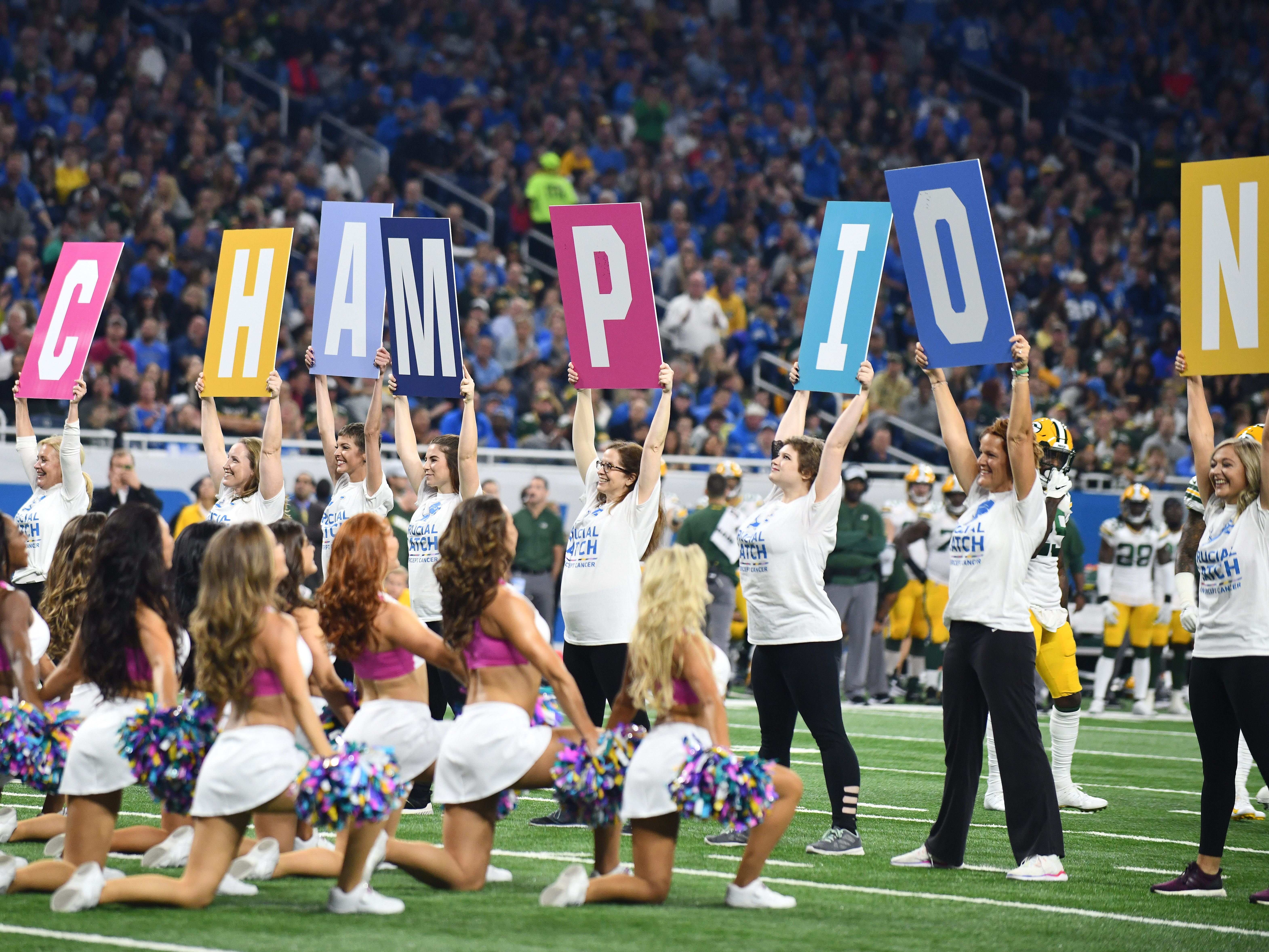 Cancer survivors are honored on the field with the Detroit Lions Cheerleaders during a break in the action in the first quarter.