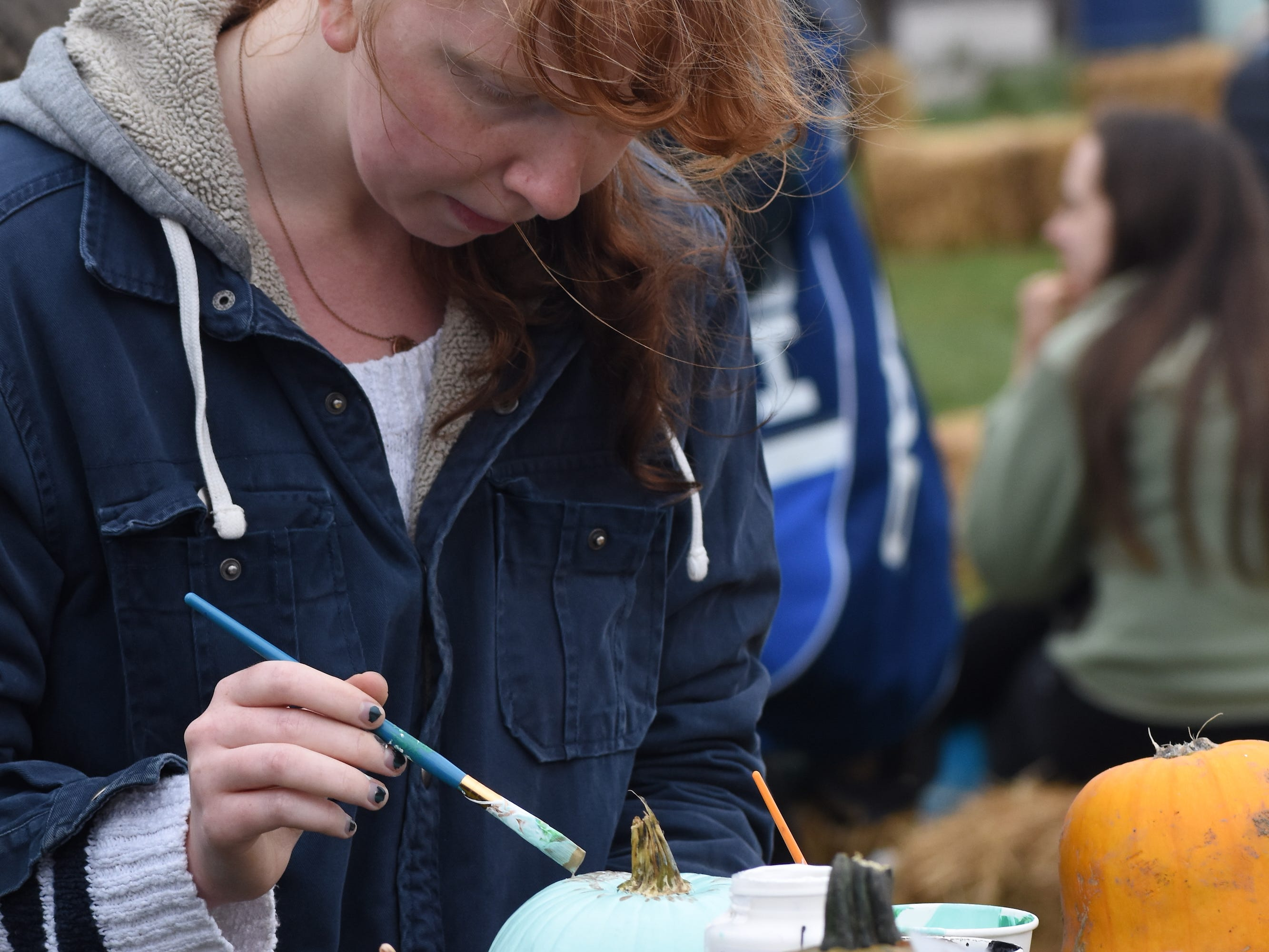 Rin Swan, of New York, paints a pumpkin at Harvest Fest. Visitors were invited to decorate a pumpkin to take with them.