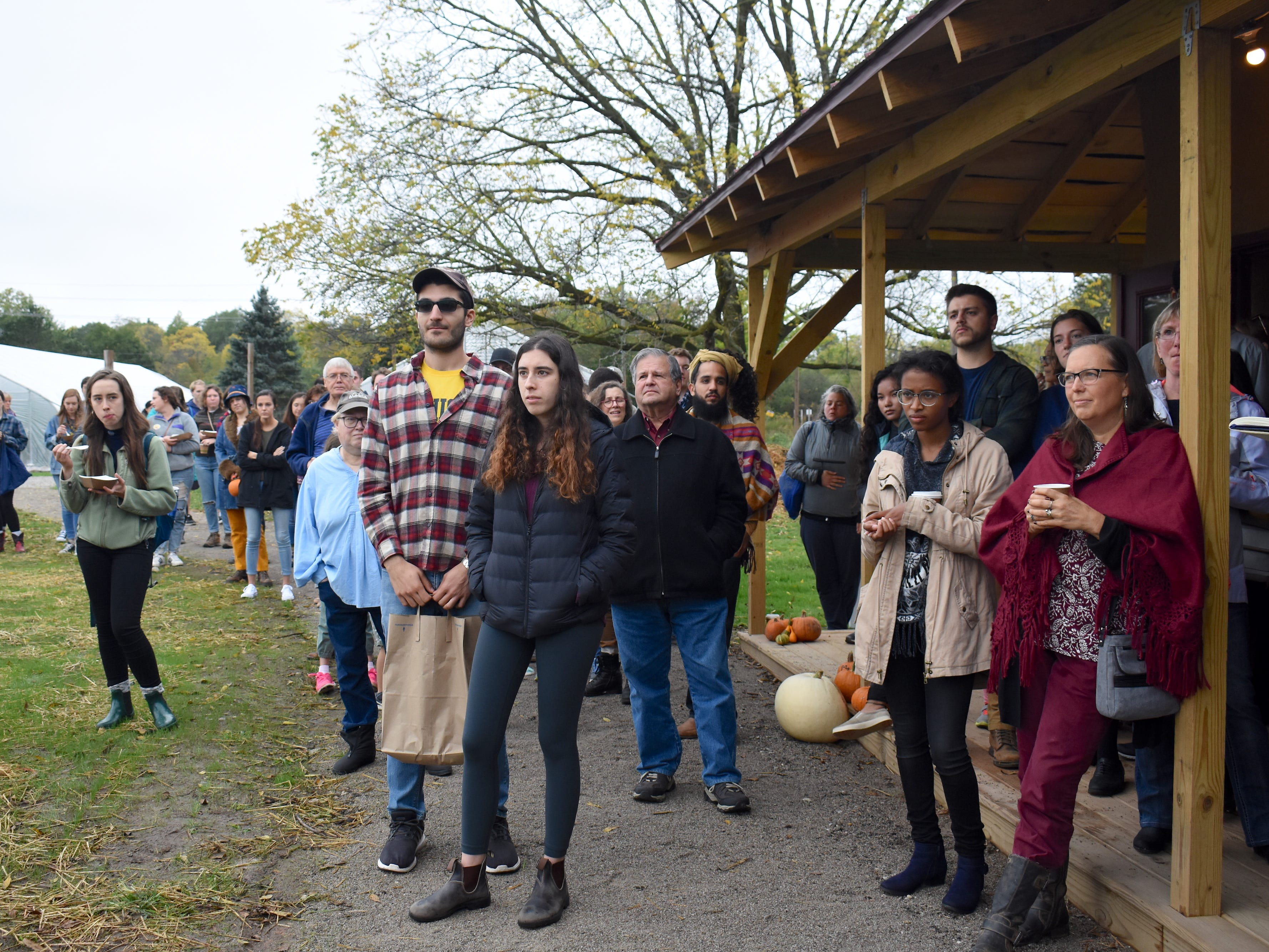 Students, university officials and guests gather outside the Straw Bale Building to celebrate its public unveiling at the Harvest Fest with a small ceremony.