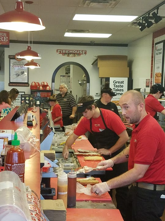 General Manager Kyle Ray, right, helps man the busy line at Firehouse Subs on Friday, October 4, 2018.