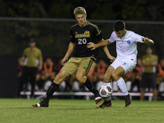 Jasper's Jackson Kabrick (left) fights for the ball during a 3A boys' soccer sectional championship last October. Castle won, 1-0.