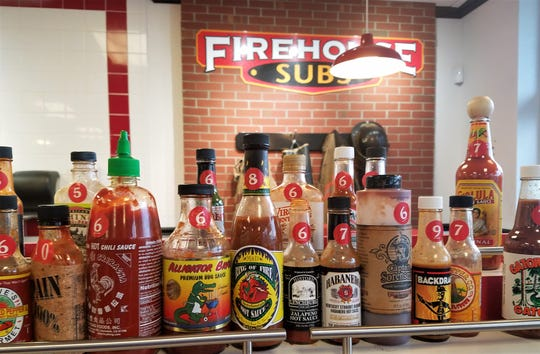 Over 25 hot sauces are labeled 1-10 according to heat level and ready to sample at Firehouse Subs on Friday, October 4, 2018.