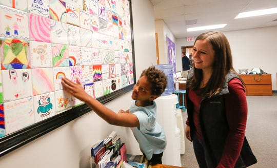 Kamari Branch and Jenna Marcoe of Fond du Lac look at tiles made by littles at the Big Brothers Big Sisters building in Fond du Lac.
