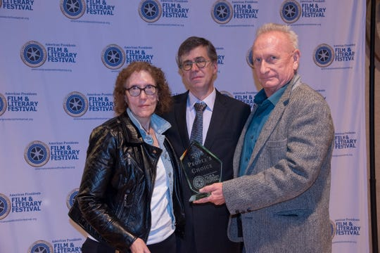 "Pam Faulkenberg, left, and Jack Cochran, right, a Fremont native, receive their award for People's Choice from Kirk Ellis, screenwriter for the HBO miniseries ""John Adams"" and keynote speaker for the event. Faulkenberg and Cochran created the short film ""Teddy Roosevelt and Fracking."""