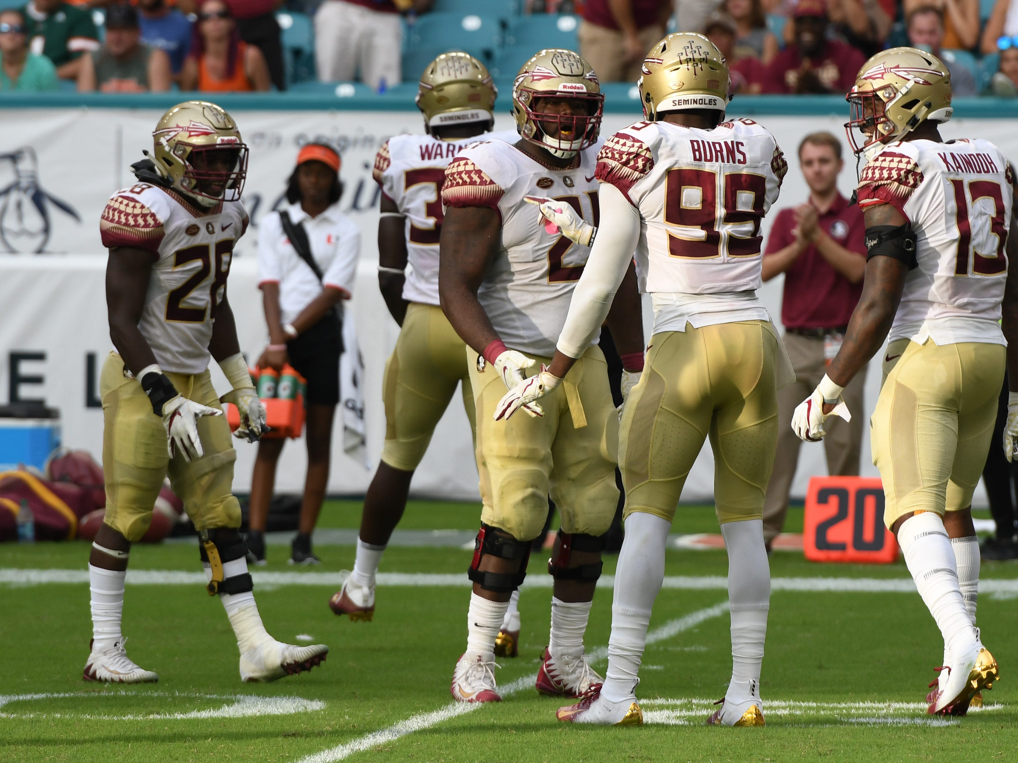 FSU sophomore noseguard Marvin Wilson (21) celebrating with his teammates after sacking the quarterback during the third quarter of FSU's game against Miami at the Hard Rock Stadium on October 6th 2018.