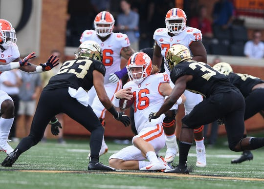 Clemson quarterback Trevor Lawrence (16) slides before being hit by Wake Forest linebacker Justin Strnad (23) during the 1st quarter at BB&T Field in Winston Salem, N.C. Saturday, October 6, 2018.