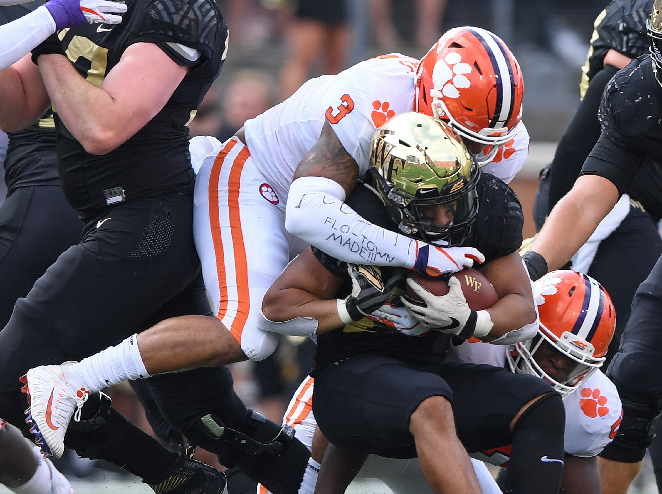 Clemson linebacker Tre Lamar (57) and defensive lineman Xavier Thomas (3) bring down Wake Forest running back Matt Colburn II (22) during the 1st quarter at BB&T Field in Winston Salem, N.C. Saturday, October 6, 2018.