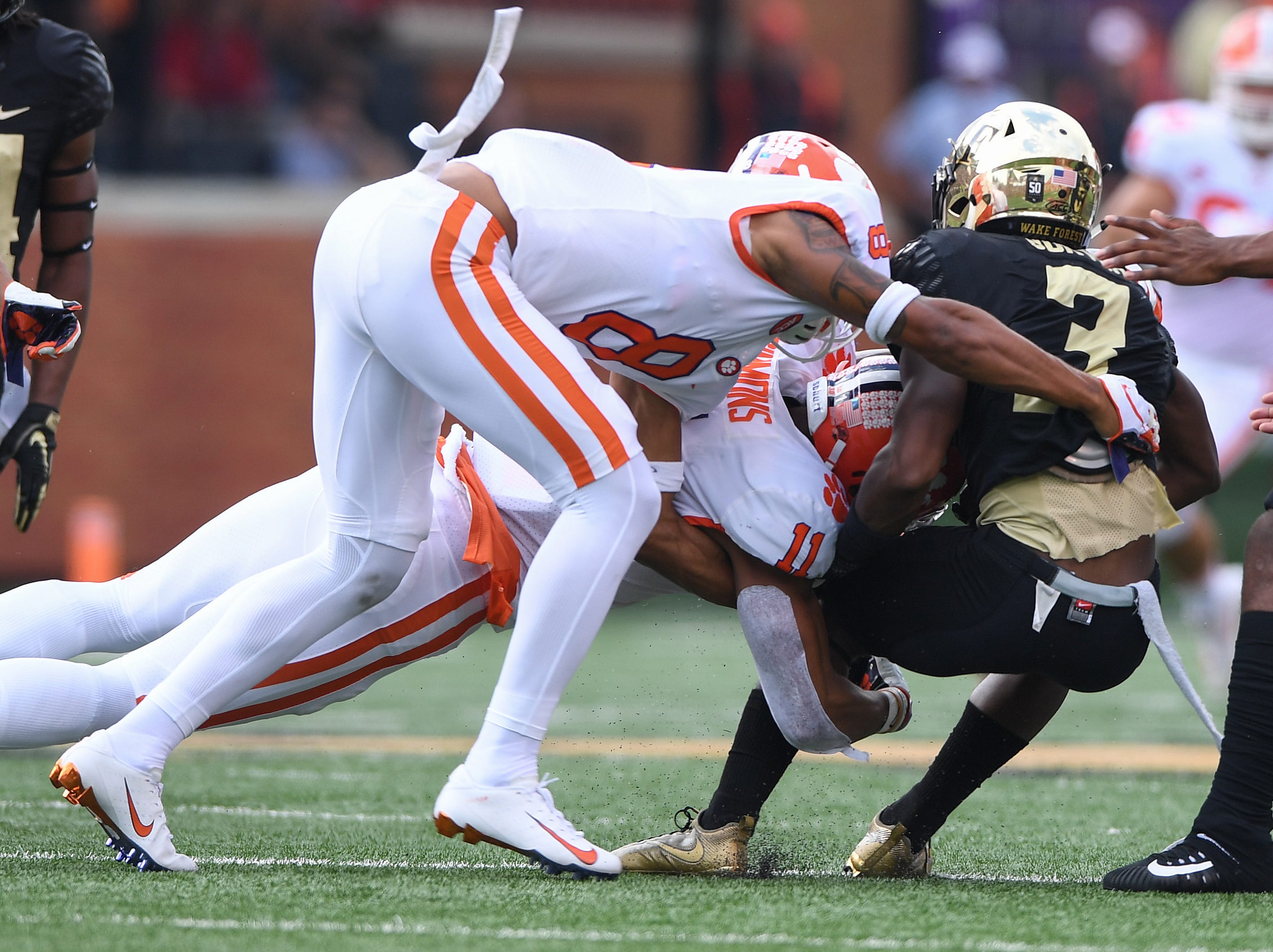 Clemson safety Isaiah Simmons (11) and defensive back A.J. Terrell (8) bring down Wake Forest wide receiver Greg Dortch (3) during the 1st quarter at BB&T Field in Winston Salem, N.C. Saturday, October 6, 2018.