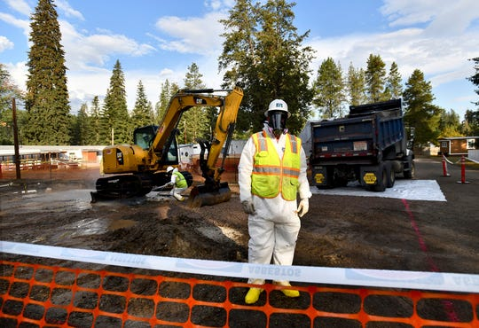 Environmental cleanup specialists work at one of the last remaining residential asbestos cleanup sites in Libby, Montana, in September of last year.
