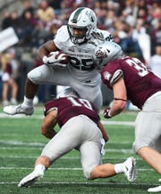 Portland State running back Sirgeo Hoffman (25) hurtles Montana safety Reid Miller (10) as Montana linebacker Dante Olson (33) prepares to hit Hoffman during the second half of an NCAA college football game Saturday, Oct. 6, 2018, in Missoula, Mont. (Colter Peterson/The Missoulian via AP)