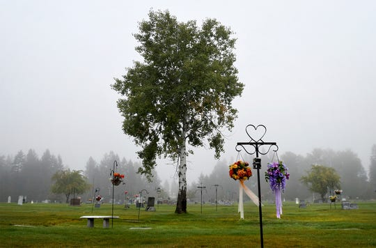 "The early-morning fog shrouds the cemetery in Libby, Montana, on a mid-September day. At least 400 deaths have been documented to be related to asbestos exposure in the town, but health officials suspect the number to be much higher. For years, the hospital was run by W.R. Grace, the same company that owned the mine, and ""asbestos"" never appeared on a death certificate in Libby. (Kurt Wilson/The Missoulian via AP)"