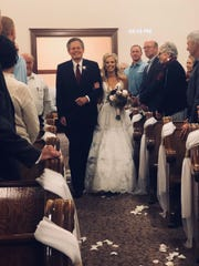 Sen. Steve Daines escorts daughter Annie down the aisle Saturday at her wedding in Montana.