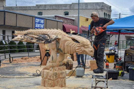 In this Saturday, Sept. 23, 2018 photo, Raimondus Uzdravis, from Lithuania, carves a dragon during the Kootenai Country Montana Chainsaw Carving Championship in Libby, Mont. (Ben Kibbey/The Western News)