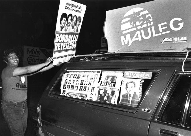 In this Nov. 5, 1986 file photo, Phillip Itliong holds up a Bordallo-Reyes sign to a passing motorist supporting the Ada-Blas team, which used the word Mauleg to campaign in its gubernatorial campaign.