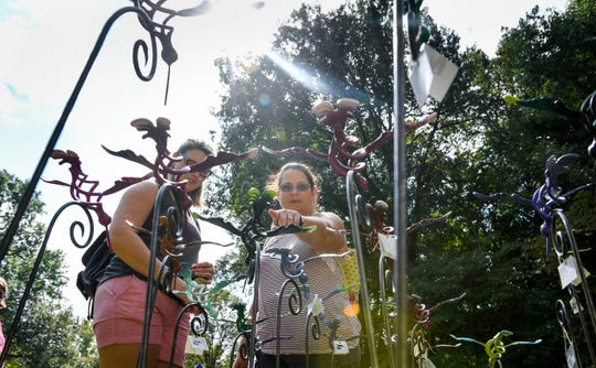 Morgan Rausch, left, and Stephanie Rausch trying to pick out a wrought iron lawn ornament at the Henderson Lions Arts and Crafts festival held at Audubon State Park Saturday, October 6, 2018.